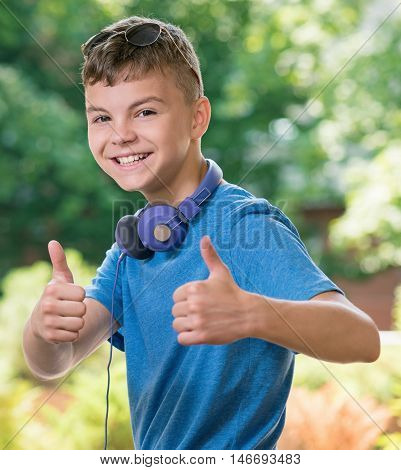 Portrait of a teen boy 12-14 year old showing thumb up gesture. Happy child having fun in park. Student with headphones and sunglasses on green background.