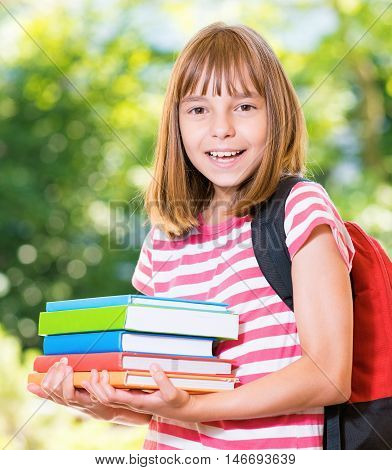 Outdoor portrait of happy girl 10-11 year old with books and backpack. Back to school concept. Beautiful schoolgirl on the first school day after vacation.