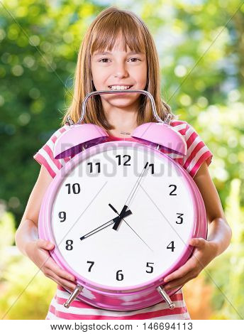 Outdoor portrait of happy girl 10-11 year old with big alarm clock. Back to school concept. Beautiful schoolgirl posing outdoors. Young student beginning of class after vacation.