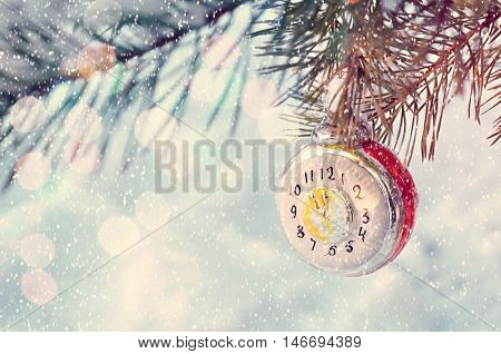 New Year and Christmas background -New Year Christmas toy on snowy fir tree branch. New Year festive card with bokeh and showflakes. Christmas and New Year background. Focus at the clock.Shallow DOF.