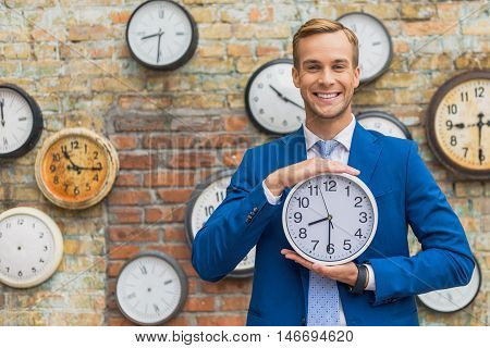 Time and business. Portrait of handsome young man holding wall clock in hands, looking at camera and smiling