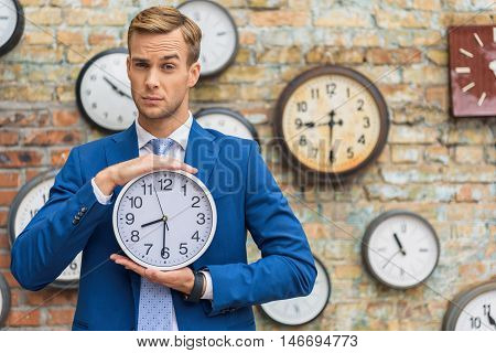 Time is money. Cropped shot of serious businessman looking at camera and holding wall clock against of brick wall with clocks