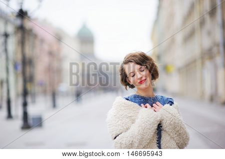Beautiful young smiling girl posing on the boulevard in the center of St. Petersburg, closing her eyes in embarrassment.