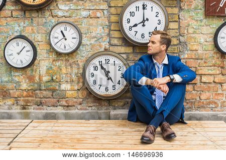 Trying to think up business solutions. Young businessman sitting on wooden floor near brick wall and looking somewhere