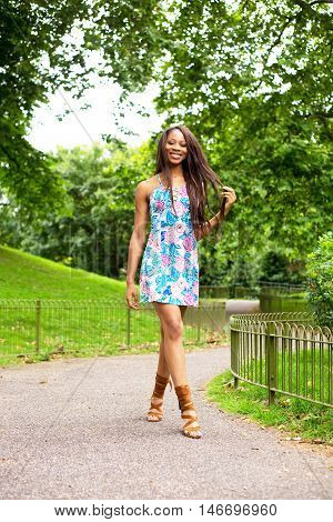 young woman enjoying a summery walk in the park