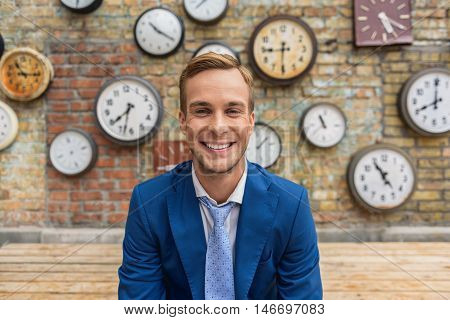 Time for change. Close up of handsome young guy standing front brick wall, looking at camera and joyfully smiling