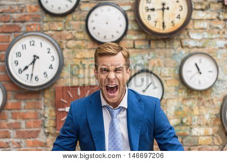 This is unacceptable. Close up of furious young businessman screaming into camera against of brick wall with clocks