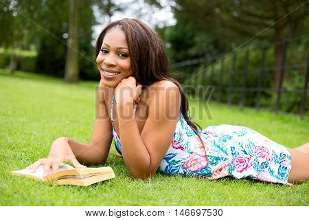 young woman in the park with a book