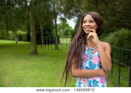 a thoughtful young woman looking pensive outdoors