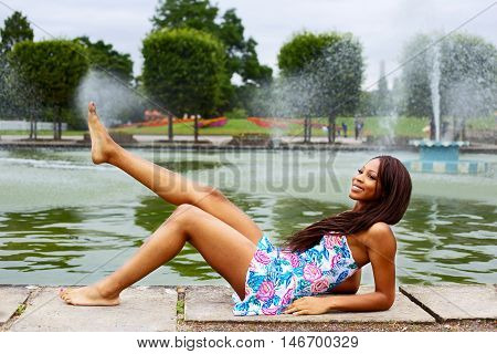 young woman sitting by the lake showing off her legs.