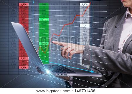 Woman trader working on laptop in stock trading concept