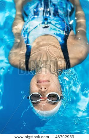 Vertical close-up photo of female swimmer in the swimming pool. Girl swims on her back with closed eyes. She wears a blue swimsuit, a white swim cap and swim glasses. Shoot from the top.