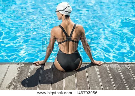Backside view of girl who sits on the pool side in the swimming pool outdoors. She wears a black swimsuit, a white swim cap and swim glasses. Her head turned to the left side, hands on the pool side.