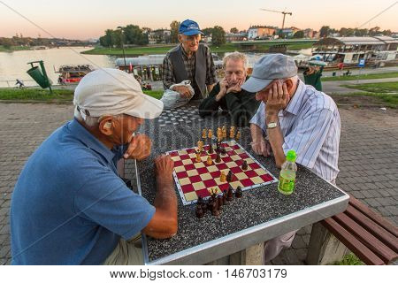 KRAKOW, POLAND - FEB 8, 2016: Unidentified elderly men play chess on the embankment of Vistula. There are about 40 parks in Krakow including dozens of gardens and forests.