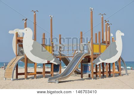 toboggan with figures seagull shaped in the beach