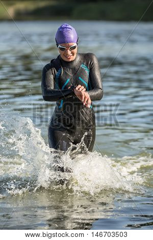 Pretty female runner runs on the water outdoors. She wears dark swim run suit, violet cap, swim glasses. Girl looks at the stopwatch. Water splashes are around her body. Sun shines at her body.