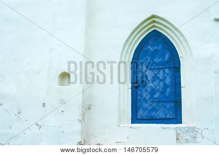 Architecture view of architecture details - aged dark blue metal forged door with arcade on the white stone wall. Architecture background.