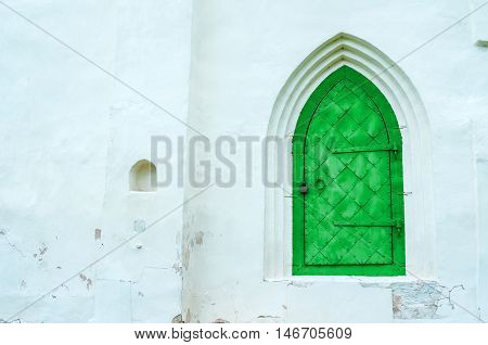 Architecture view of architecture details - aged bright green metal forged door with arcade on the white stone wall. Architecture background.