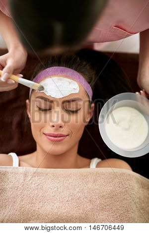 Smiling woman on cosmetic treatment of her face skin, cosmetician applying facial mask with brush