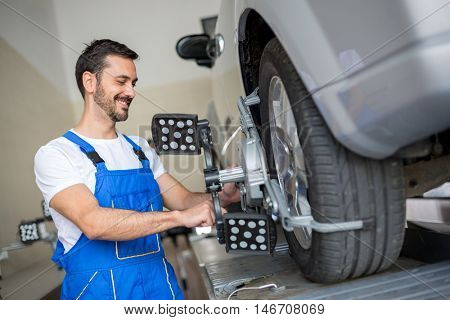 auto mechanic at wheel alignment work with sensor