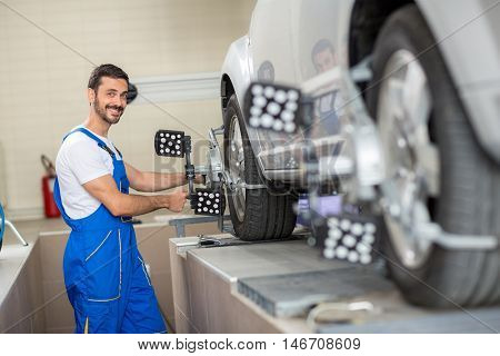 Satisfied auto mechanic at wheel alignment work with sensor