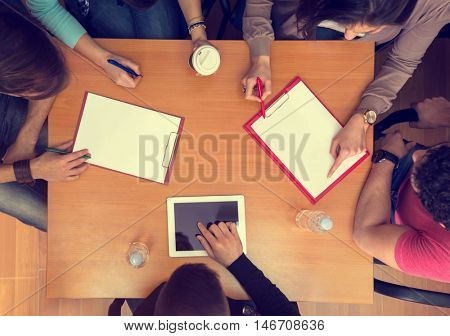 Top view of working table with students, tablet and statistics in teamwork