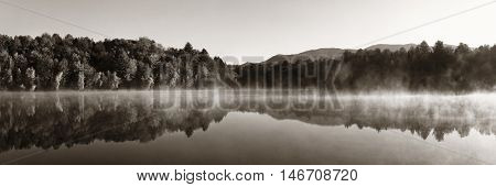 Lake fog panorama with Autumn foliage and mountains with reflection in New England Stowe