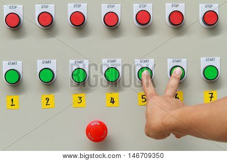 Forefinger and middle finger touch on green start button on control panel of automatic machine.