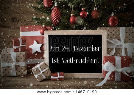 Nostalgic Card For Seasons Greetings. Christmas Tree With Balls And Snowflakes. Gifts In Front Of Wooden Background. Chalkboard With German Text Am 24. Dezember Ist Weihnachten Means Merry Christmas