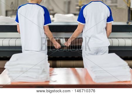 Laundry worker puts ironed textile in ironing machine