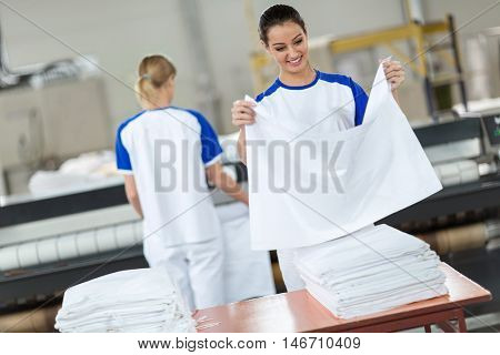 Employee agree ironing textiles in dry cleaner