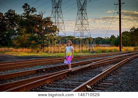 little girl with the railroad. Girl near railroad tracks sky clouds