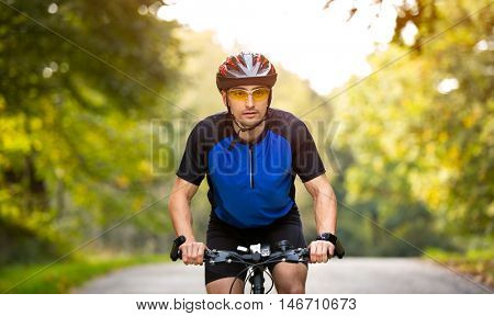 Young cyclists ride bike with helmet, looking at camera