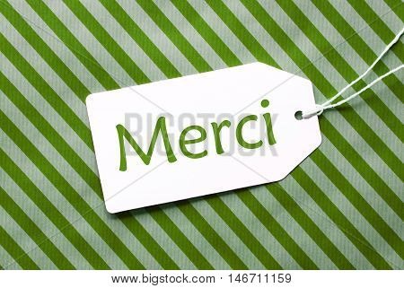 One Label On A Green Striped Wrapping Paper. Textured Background. Tag With Ribbon. French Text Merci Means Thank You