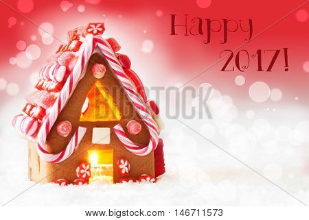 Gingerbread House In Snowy Scenery As Christmas Decoration. Candlelight For Romantic Atmosphere. Red Background With Bokeh Effect. English Text Happy 2017 For Happy New Year