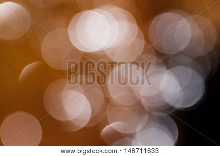 Blurred white circles on a reddish brown background