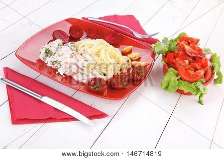 mediterranean cuisine: fresh rose wild salmon baked in cream cheese sauce with italian pasta and red hot pepper on plate over white wooden table with vegetable salad