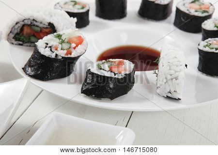 maki uramaki and onigiri sushi rolls with ginger and japan vinegar and sticks on plates over white wooden table