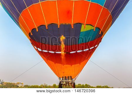 Close up of hot air balloon burner flame glowing at sunset time.