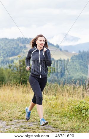 Young Fitness Woman Trail Running In Mountains
