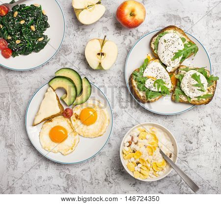 Helpful and tasty breakfast from different of dishes - fried egg poached eggs avocado apple spinach salad and muesli on light surface top view