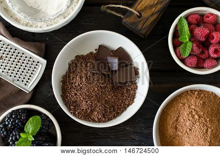 Food ingredients for cooking chocolate dessert with fruit on dark wooden table close up top view