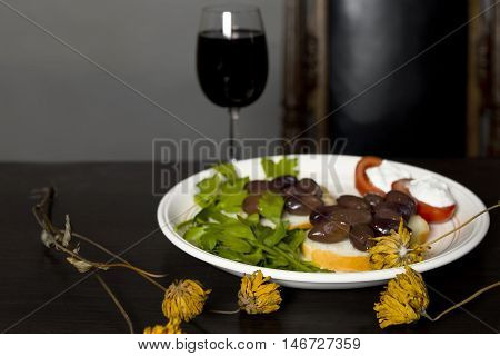 Yellow flowers in focus and garnish with a glass of red wine in the background studio shot