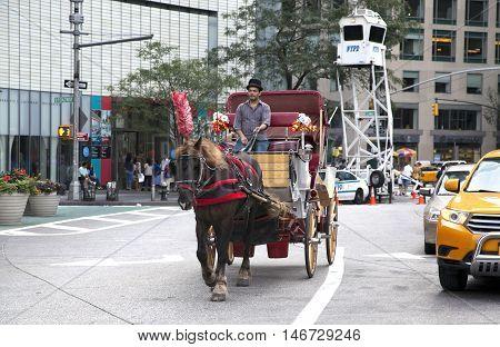 NEW YORK NEW YORK - AUGUST 21: Man on horse drawn carriage rides through Columbus Circle. Taken August 21 2015 in New York.