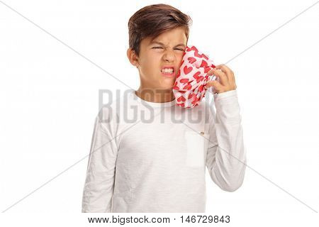 Little boy experiencing a toothache and holding an ice pack isolated on white background