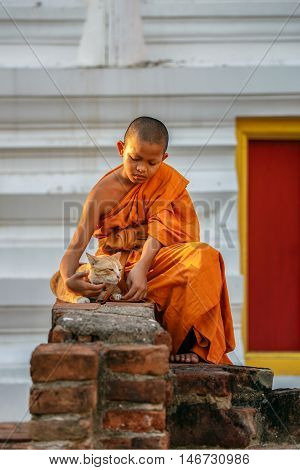Young novice monks playing cat in old temple at Ayutthaya Province Thailand