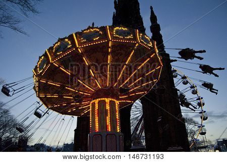 Christmas scene in Princes Street in central Edinburgh Scotland UK. Kids on a fairground ride in front of the Scott Monument -- Picture by Jonathan Mitchell | Lightroom Photos