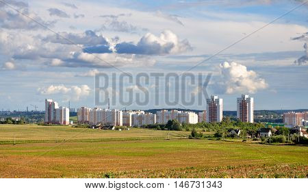 City landscape. Modern residential district. Different high-rise apartment buildings and green field in the foreground.
