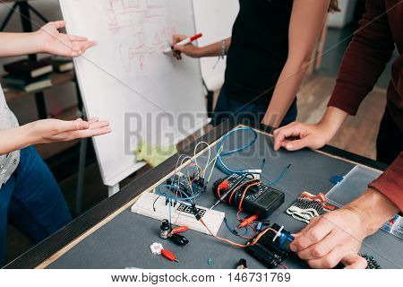 Electronics development according formula. Connection of electronic components and noticing it on whiteboard in laboratory, teamwork concept