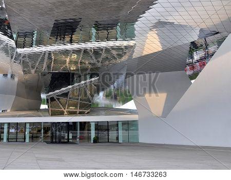 Stuttgart, Germany - April 21, 2014: Entrance to modern building Porsche car Museum in Stuttgart. Mirrored glass canopy at the large white pillars.